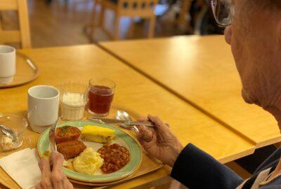 En äldre dam som sitter och äter.
