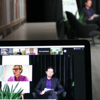 En datorskärm i förgrunden och en suddig person i bakgrunden, som håller i ett webinarie