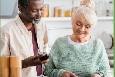 En svart man och en gråhårig kvinna lagar mat tillsammans.